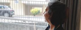 Persona en su casa mira por la ventana