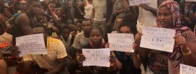 Personas en el barco con carteles en los que piden ayuda