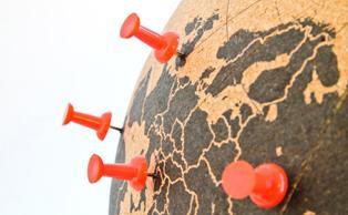 Imagen del mundo marcado con chinchetas