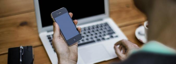 Una persona manejando un ordenador y un móvil