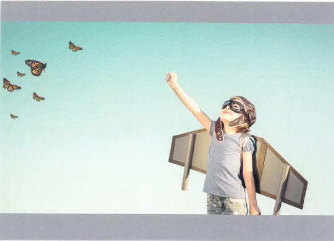 Postal con una niña o niño con disfraz de avión, gafas de aviación y gorro. Al fondo cielo y a la izquierda mariposas