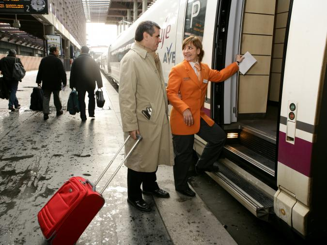 una persona del servicio Ilunion, con chaqueta naranja, acompaña a otra persona a subir a un tren